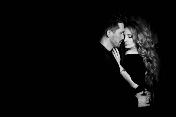 schönes paar in liebe umarmt vor schwarzem hintergrund. studio schwarz / weiss portraitfoto ein blondes mädchen und ein mann mit kurzen haaren. zum valentinstag. lieben ehepaar. familienglück - schwarze romantik stock-fotos und bilder