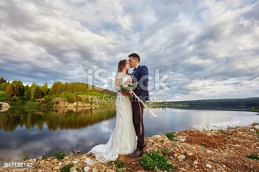 Beautiful couple in love kissing while standing on ground by lake. Wedding couple at sunset, blue cloud sky, love and tender feelings. Loving couple resting. Wedding ceremony outdoors. Perfect couple