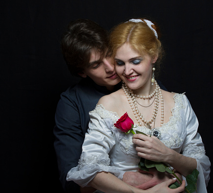 Beautiful couple in retro style. A man hugs a woman. Girl in a white dress with a red rose on a background of a man.