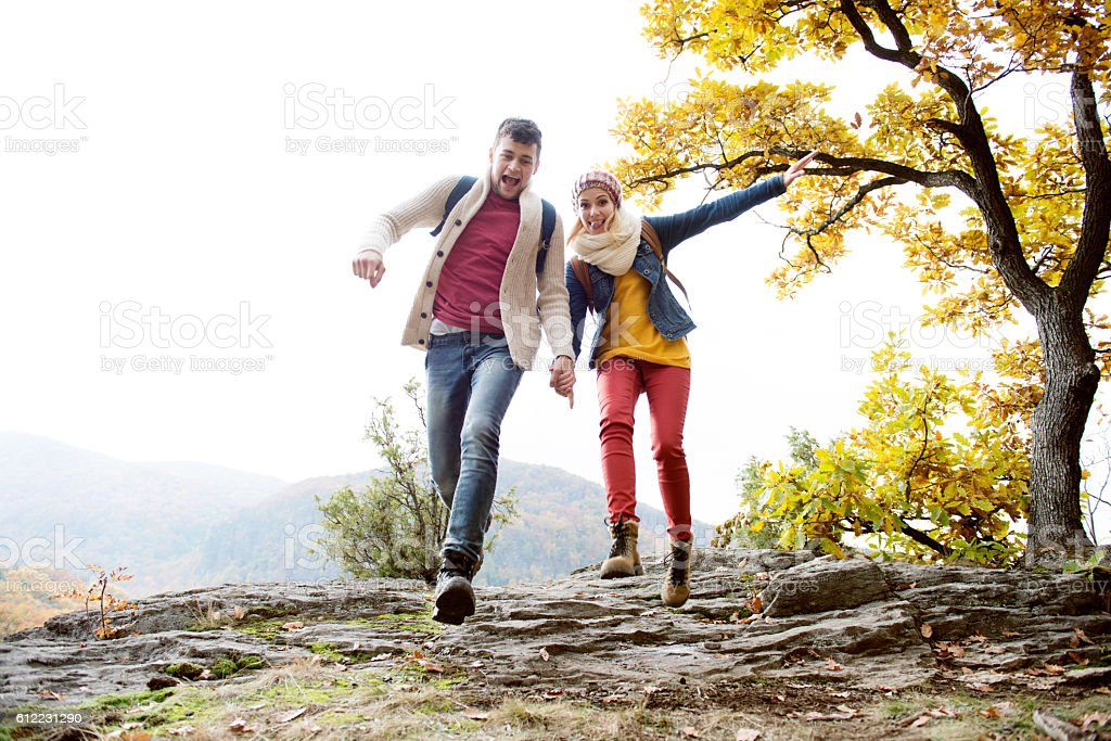 Beautiful couple in sunny autumn nature, running on a rock stock photo