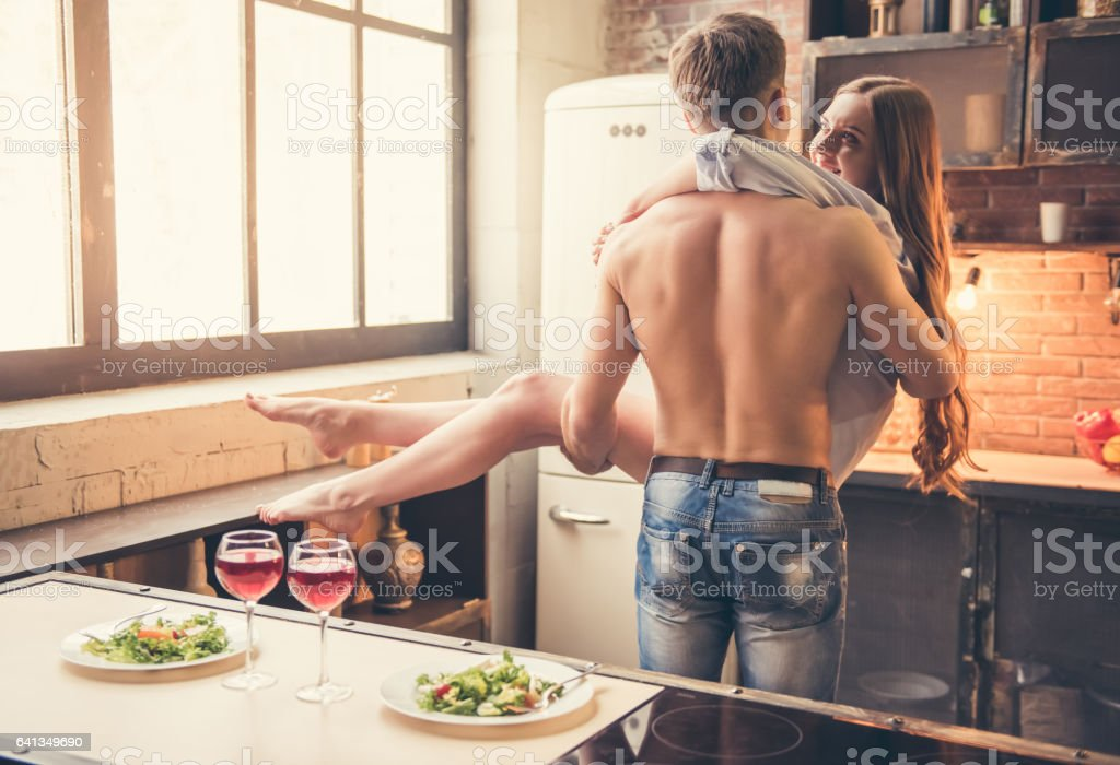 Beautiful couple in the kitchen stock photo