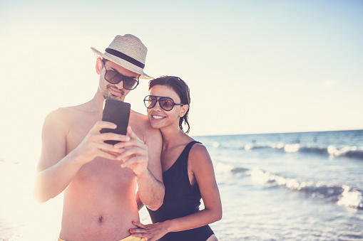 617378218 istock photo Beautiful Couple Is Making Video Call On The Beach 1060907226