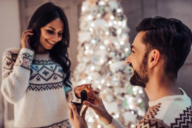 hermosa pareja está esperando el año nuevo juntos cerca de hermoso árbol de navidad en casa. - prometido fotografías e imágenes de stock
