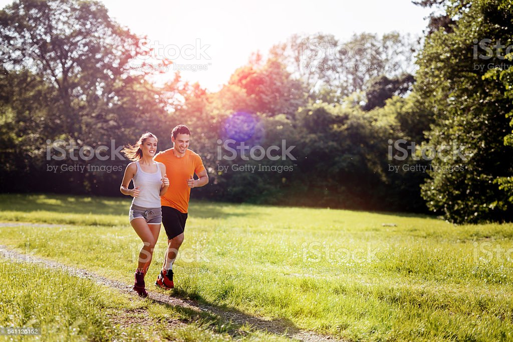 Beautiful couple jogging in nature stock photo