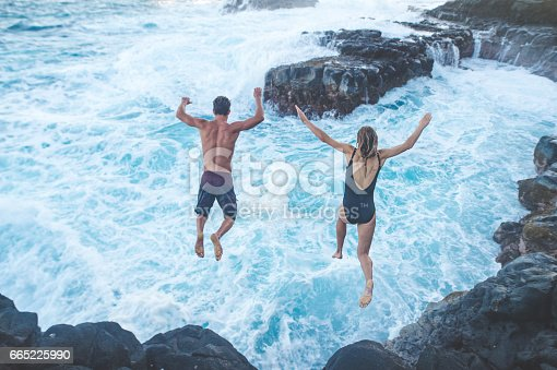 Beautiful couple jumping off a cliff into the turbulent ocean
