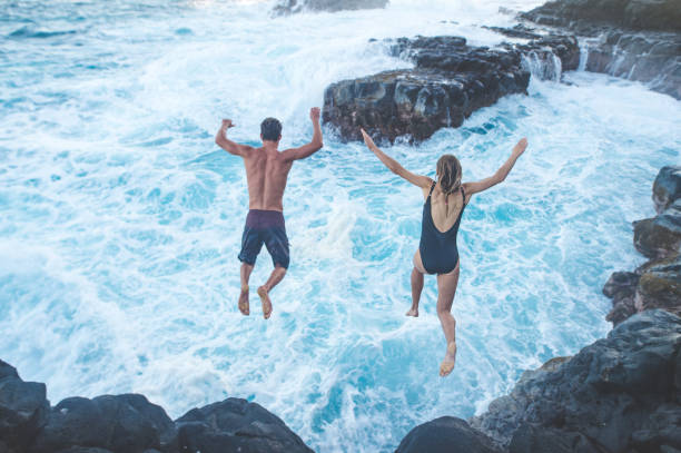 Beautiful couple jumping off cliff into ocean stock photo