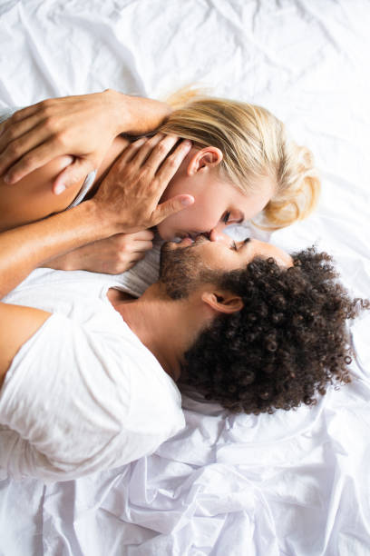 Beautiful couple kissing and lying in bed stock photo