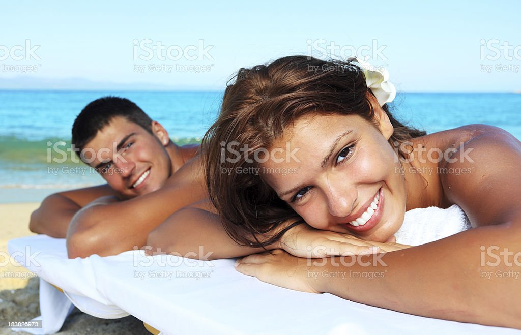 Beautiful couple lying after a massage at the beach. stock photo