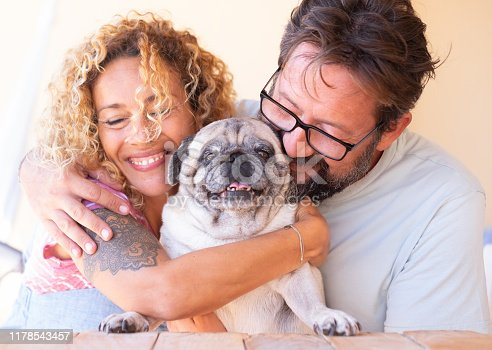 Beautiful couple man and woman in love with their clear pug dog. Forever friends. United and happy family. Smiling. Wooden table on terrace field