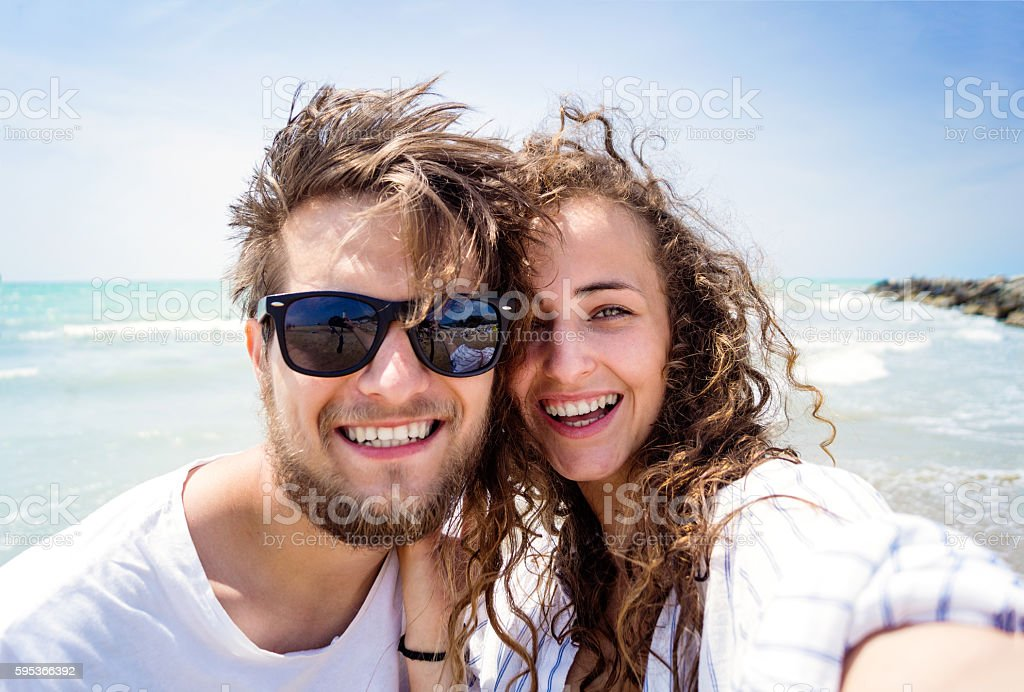 Beautiful couple on beach, laughing, taking selfie, smiling stock photo