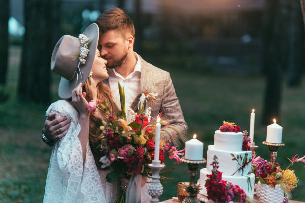 schönes paar auf hochzeit stehen in der nähe von kuchen und kerzen - modetorten stock-fotos und bilder
