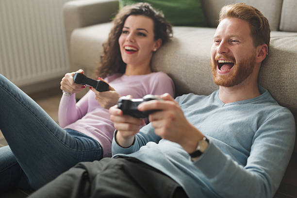 beautiful couple playing video games on console - hobby's stockfoto's en -beelden