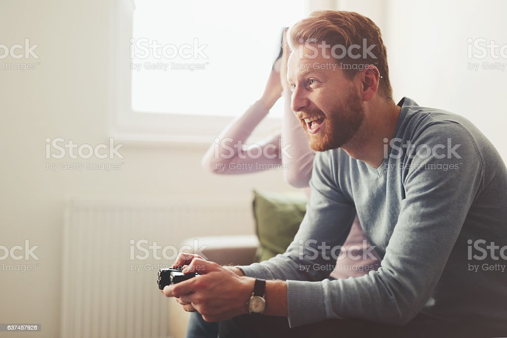 Beautiful couple playing video games on console stock photo
