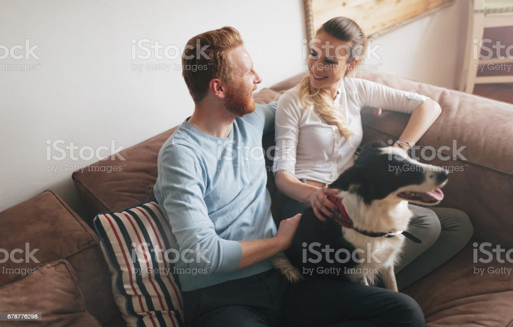 Beautiful couple relaxing at home and loving their pet royalty-free stock photo