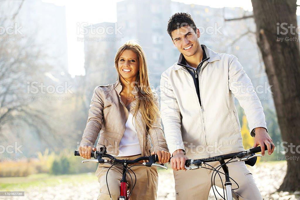 Beautiful couple rides bikes on a autumn day royalty-free stock photo