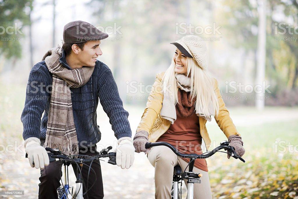 Beautiful couple rides bikes on a sunny autumn day. royalty-free stock photo