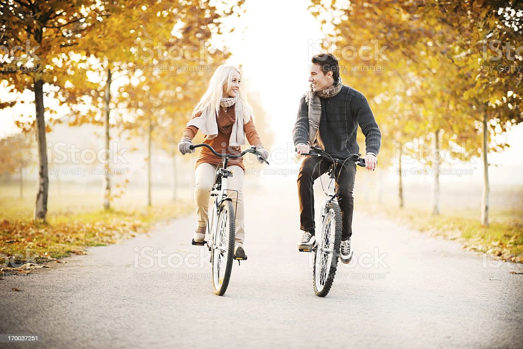 Beautiful couple rides bikes on autumn day. royalty-free stock photo