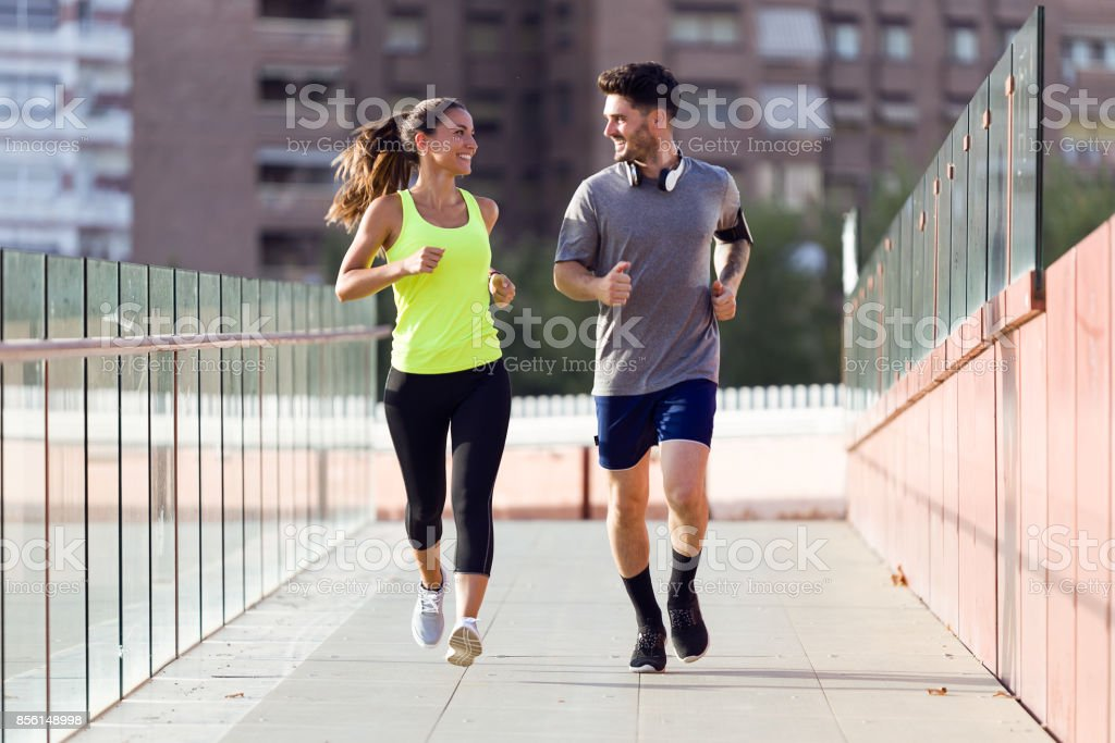 Beautiful couple running in the street. stock photo