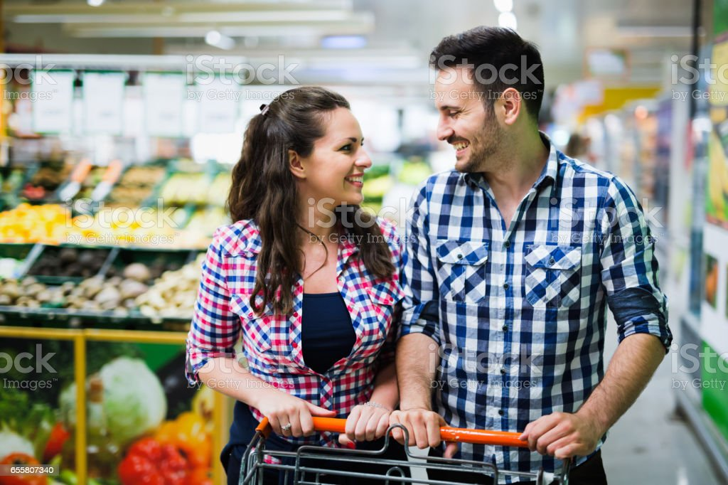 Beautiful Couple Shopping In Supermarket While Carrying