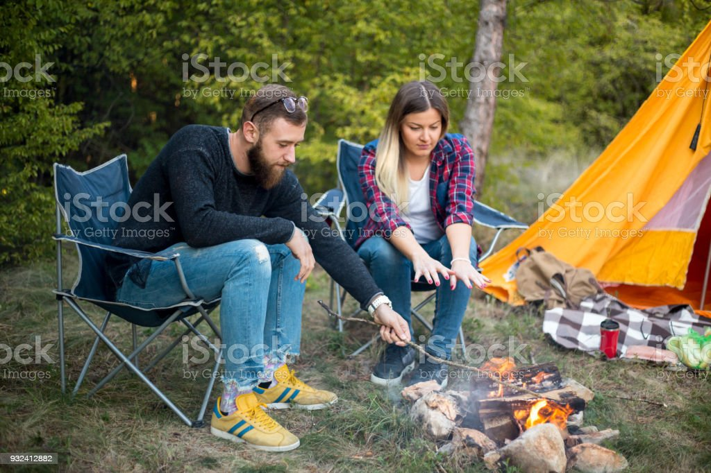Beautiful couple, sitting, camping around the campfire. On the background with a tent The man flicks the fire with a stick. stock photo