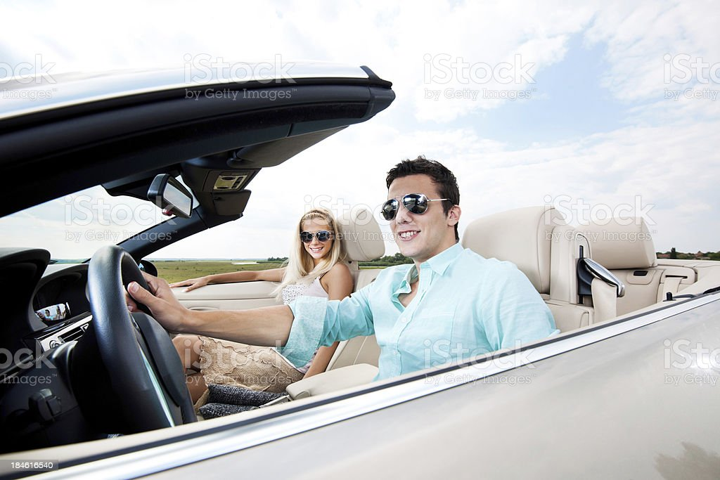 Beautiful couple sitting in their Convertible car. royalty-free stock photo