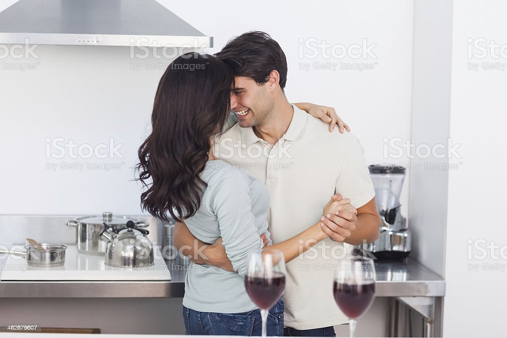 Beautiful couple slow dancing in the kitchen stock photo