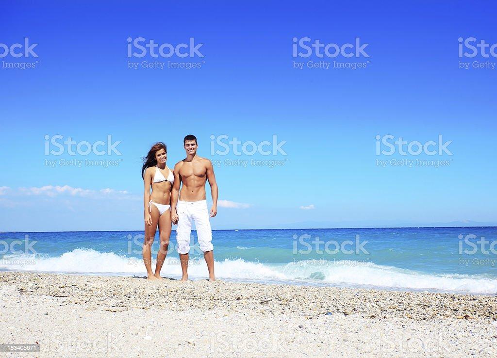 Schönes paar steht und sucht in die Kamera am Strand. – Foto