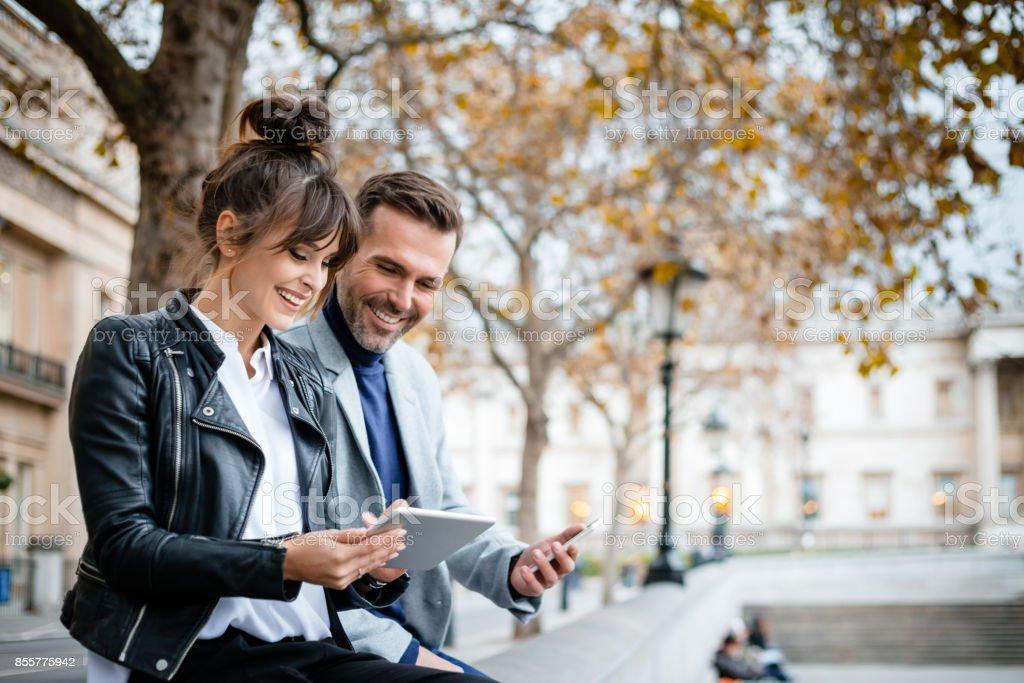 Schönes Paar mit digital-Tablette am Trafalgar Square in London, Herbstsaison – Foto
