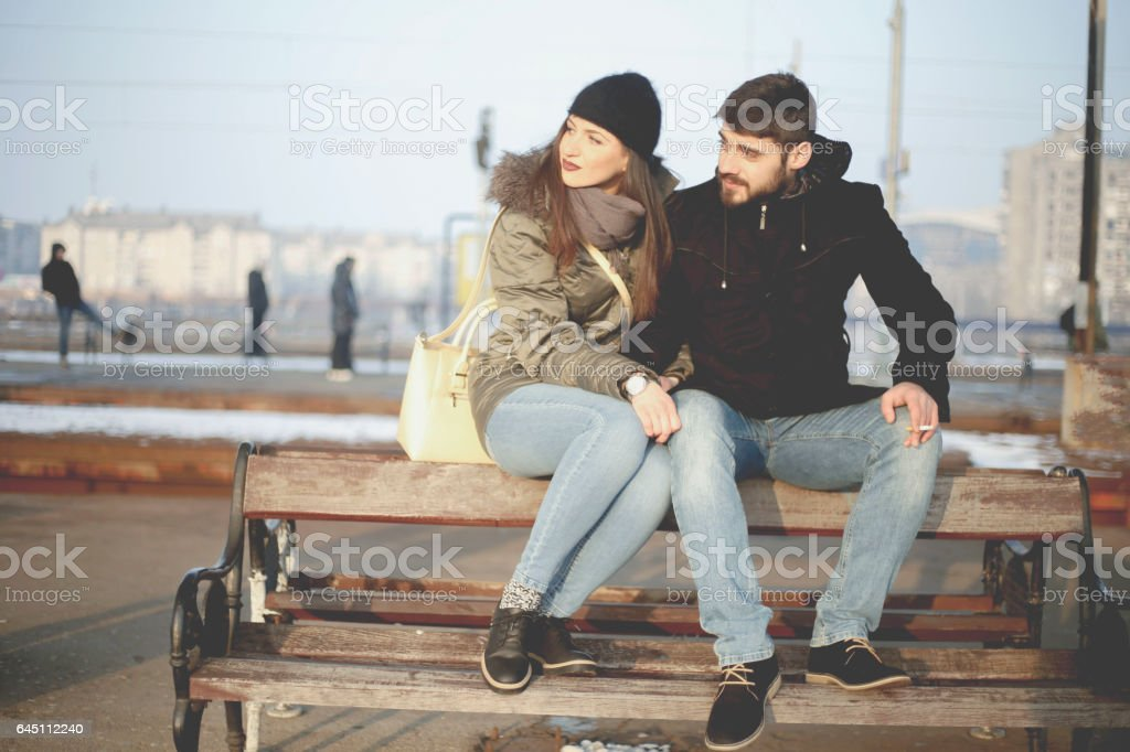 Beautiful couple waitin for train on railway station stock photo