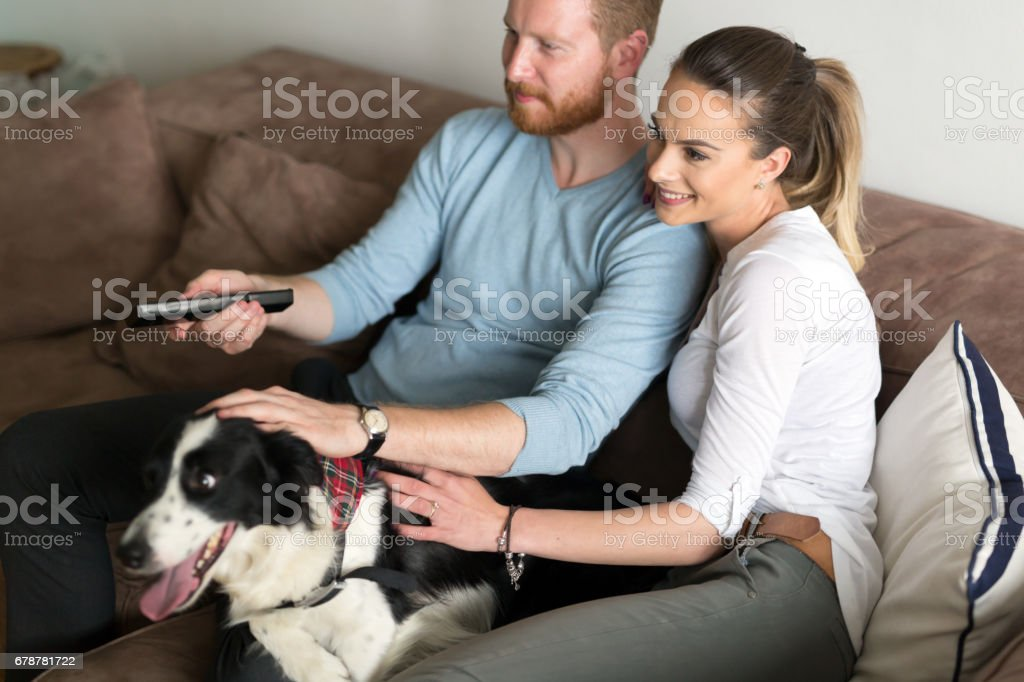 Beautiful couple watching television at home with their dog on sofa photo libre de droits