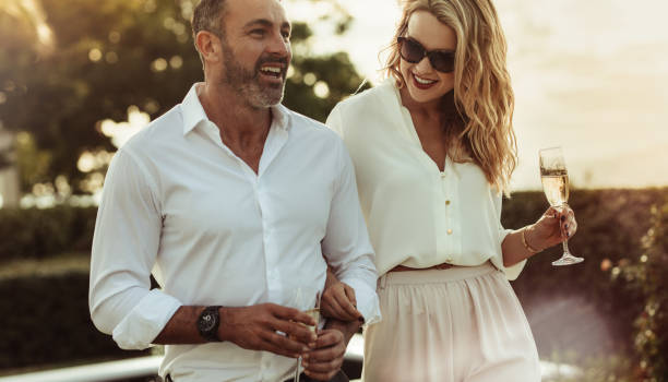 Beautiful couple with a glass of wine outdoors Cheerful man and woman with a drink outdoors. Wealthy couple together with a glass of wine. affluent lifestyles stock pictures, royalty-free photos & images