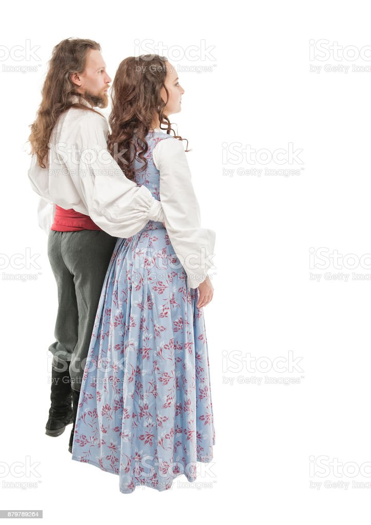 Beautiful couple woman and man in medieval clothes. Turn pose stock photo