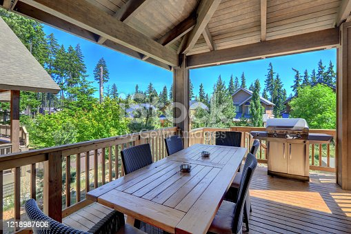 Beautiful covered deck with large luxury dining room table with grill and railings. Lots of pine trees.