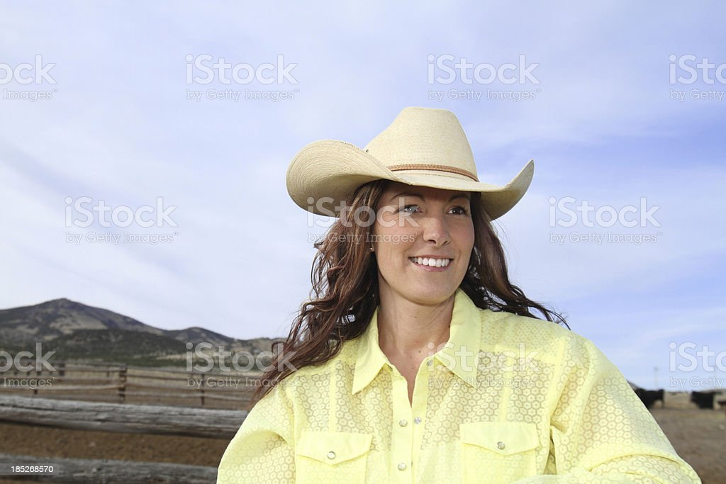 Beautiful Cowgirl with Ranch and Blue Sky Background royalty-free stock photo