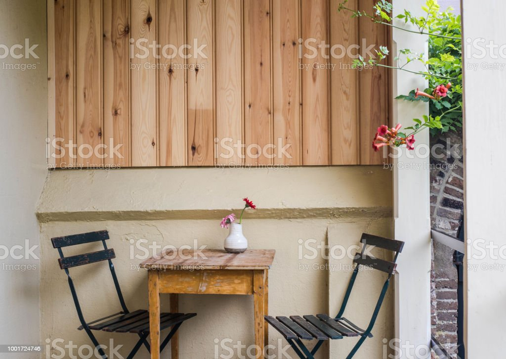 Beautiful cozy terrace or balcony with small table, chair and flowers. Toned image