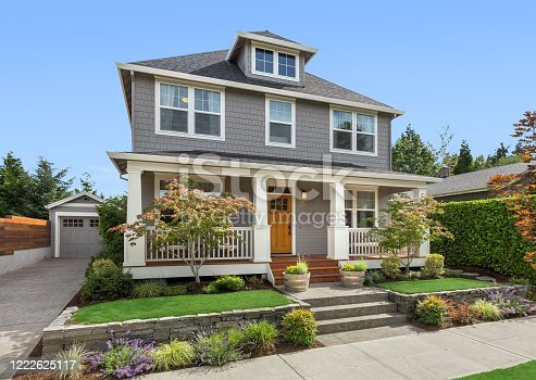 istock Beautiful craftsman home exterior on bright sunny day with green grass and blue sky 1222625117