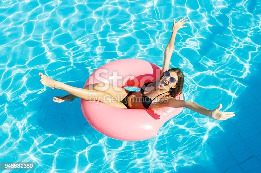 istock Beautiful crazy woman relaxing on inflatable ring in blue swimming pool 948632380