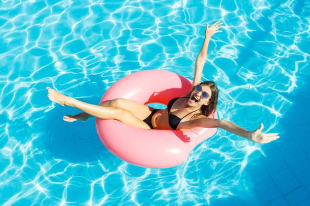 linda mulher louca relaxando no anel inflável em azul piscina - biquíni - fotografias e filmes do acervo