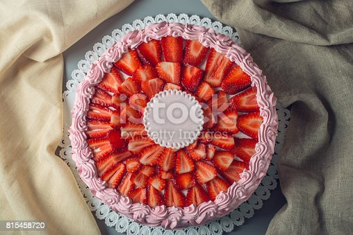 Beautiful cream cake on top decorated with sliced strawberries and place for text. The concept of desserts for the holidays