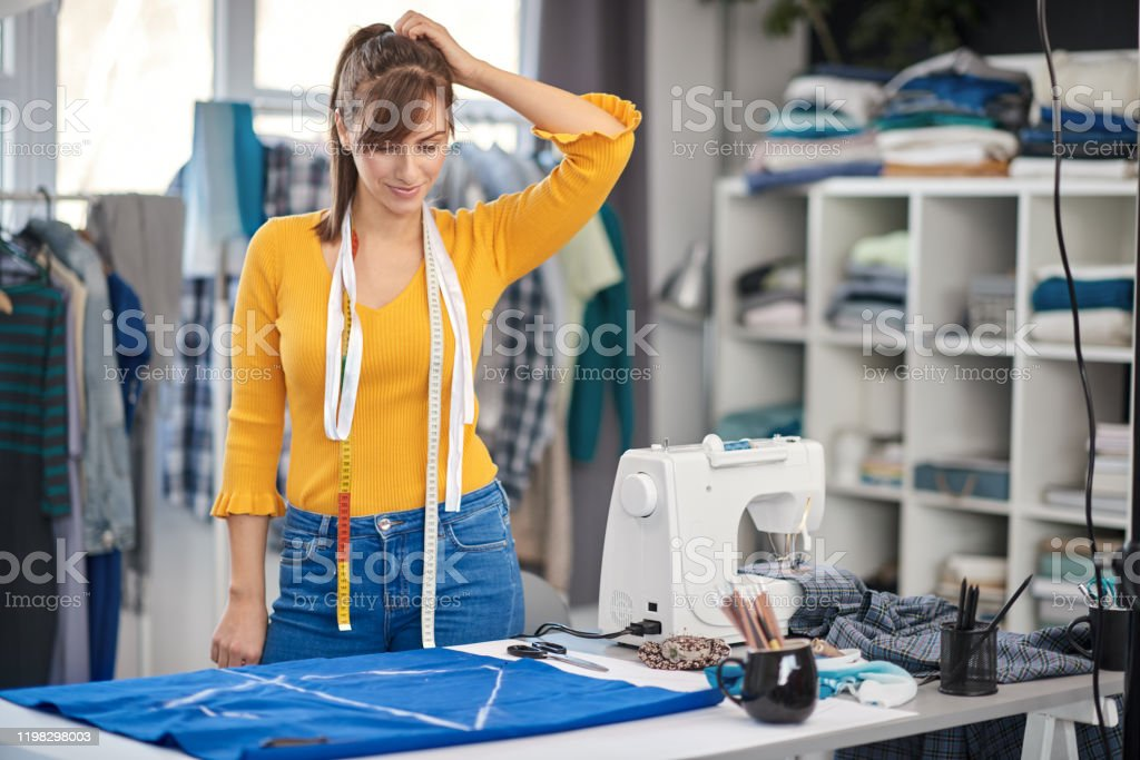 Beautiful Creative Caucasian Fashion Designer Standing In Her Studio And Looking At Textile Stock Photo Download Image Now Istock