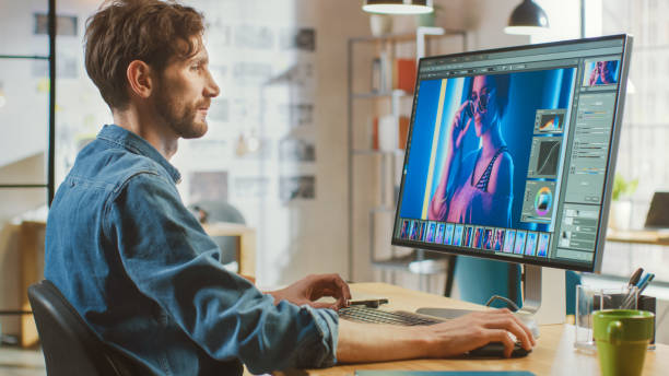 Schöne kreative männliche Video-Editor mit Bart und Jeans Shirt funktioniert mit Filmmaterial auf seinem Personal Computer mit Big Display. Er arbeitet in einem Cool Bright Office Loft. – Foto