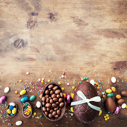 Beautiful creative photo with Chocolate Easter eggs on wooden background. Happy Easter!