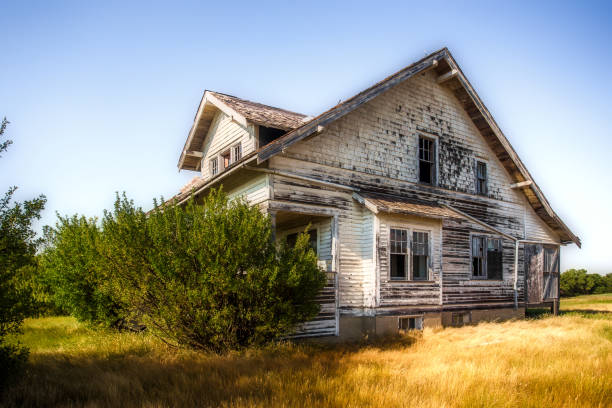 Beautiful crumbling two story farm house A large beautiful wooden two story abandoned farm house with peeling paint and broken windows in a rural summer countryside run down stock pictures, royalty-free photos & images
