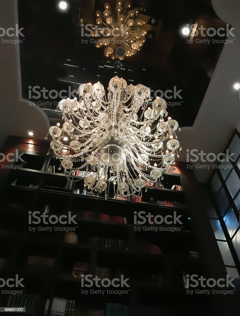 Beautiful crystal chandelier hanging to the mirror reflective ceiling for interior decoration. stock photo