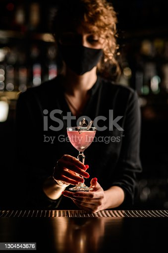 beautiful crystal glass of pink cocktail decorated with flower in the hands of attractive woman in black mask