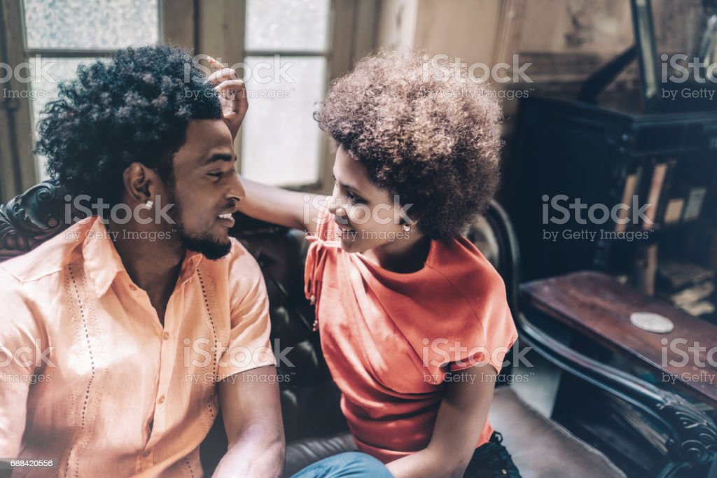 beautiful cuban couple sitting together on sofa in old house stock photo