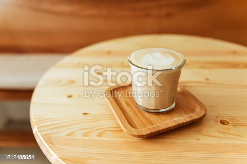 1009835562 istock photo A beautiful cup of cappuccino with latte art in the wooden space background. 1212485654