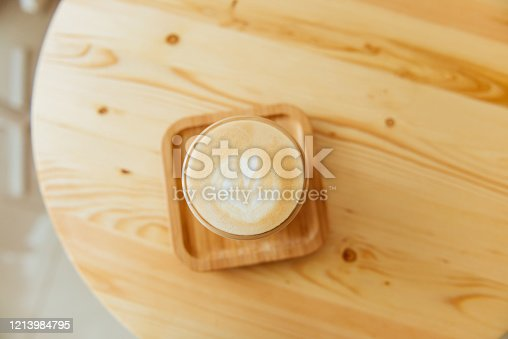1009835562 istock photo A beautiful cup of cappuccino with latte art in the wooden space background. 1213984795