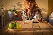 istock Beautiful curly adult woman read a book outdoor at home int errace or trendy room with wood table and tea or coffee - style lifestyle and concept of people enjoying life at home 1222164477