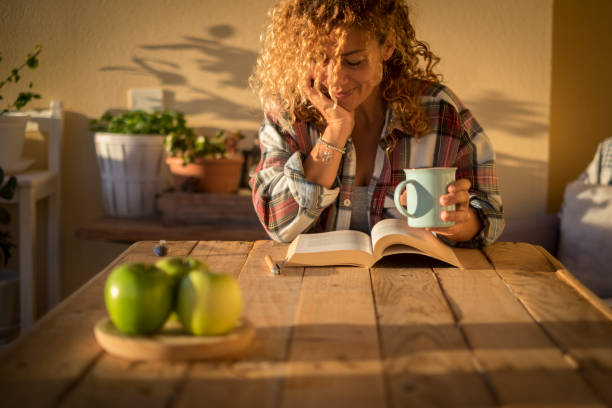 Beautiful curly adult woman read a book outdoor at home int errace or trendy room with wood table and tea or coffee - style lifestyle and concept of people enjoying life at home stock photo